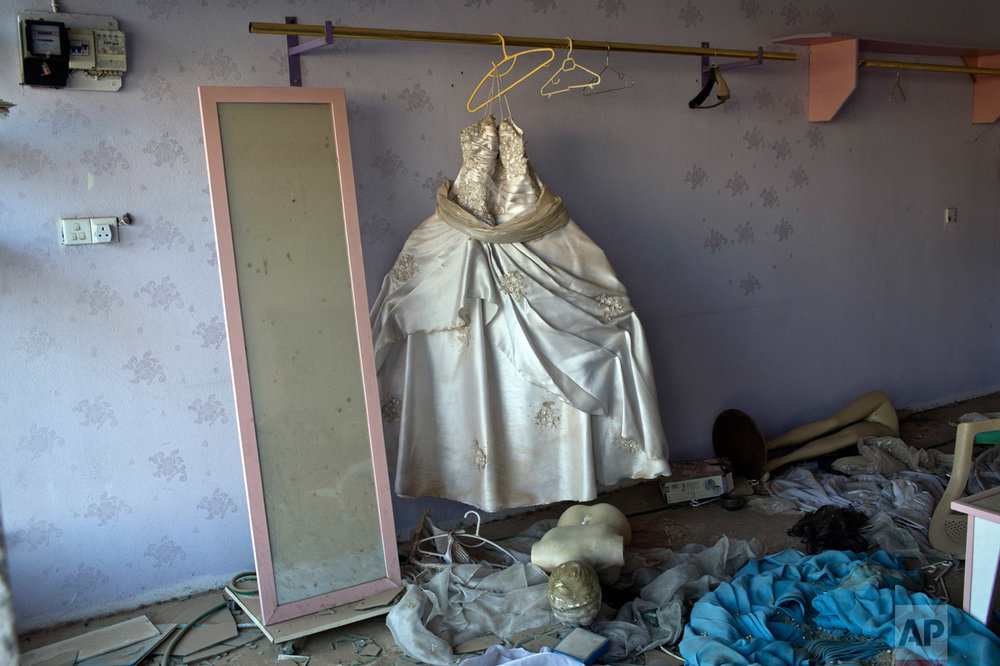A wedding gown stands in a beauty parlor damaged in clashes between Iraqi security forces and Islamic State fighters in Bartella, Iraq, Saturday, Oct. 22, 2016. (AP Photo/Marko Drobnjakovic)