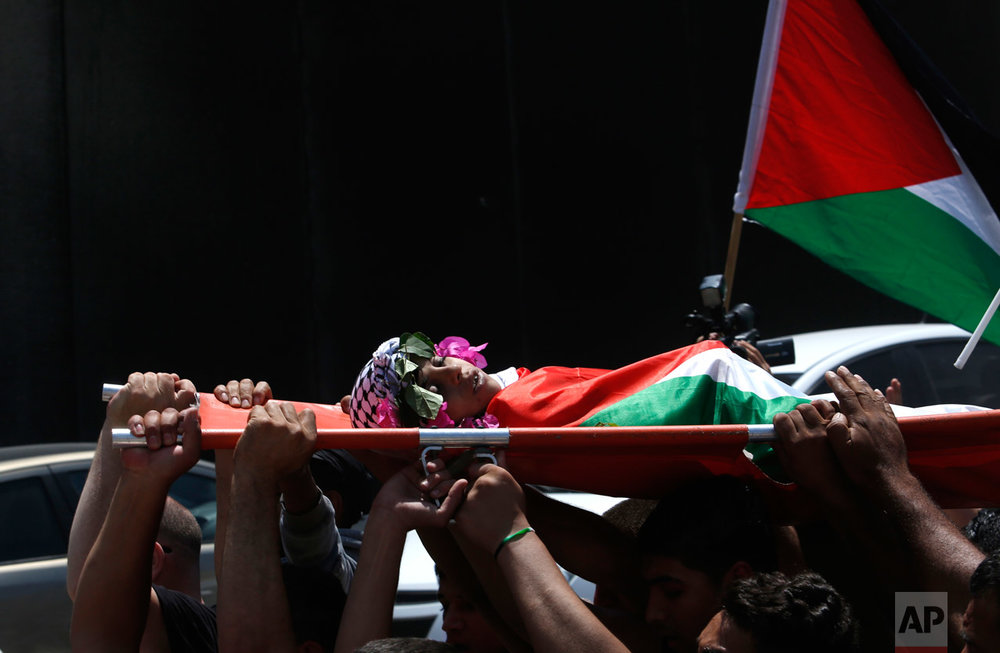 Mourners walk past the Israeli barrier as they carry the body of Muhey al-Tabakhi, 12, during his funeral in the West Bank town of Al-Ram, near Jerusalem, Wednesday, July 20, 2016. A Palestinian hospital official says the boy was killed after clashes erupted between Israeli forces and protesters in the West Bank. Ramallah hospital director Ahmad Bitawi says the boy was killed by a bullet to the chest. Israeli police deny that live fire was used against protesters.(AP Photo/Nasser Shiyoukhi)