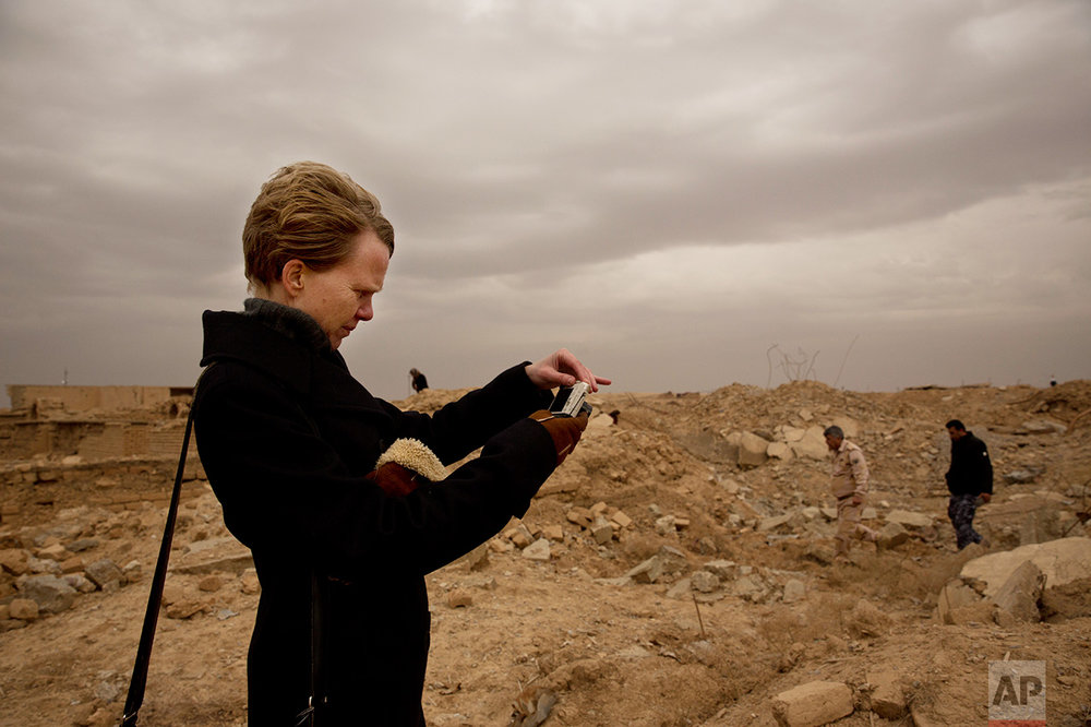 UNESCO's Iraq representative Louise Haxthausen documents the damage wreaked by the Islamic State group at the ancient site of Nimrud, Iraq, in this Wednesday, Dec. 14, 2016 photo. More than a month after the extremists were driven out, the site is still in danger, with the wreckage unprotected and vulnerable to being stolen. (AP Photo/Maya Alleruzzo)