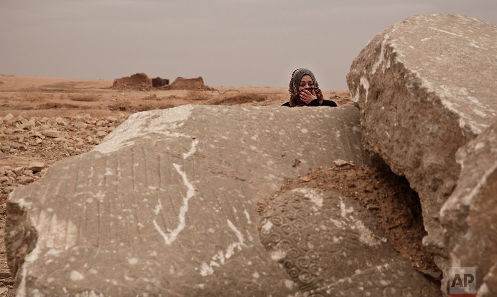 Iraqi archaeologist Layla Salih examines the remains of a statue of a lamassu, a mythical winged bull, destroyed by Islamic State group militants in the ancient site of Nimrud, Iraq, in this Wednesday, Dec. 14, 2016 photo. Salih is perhaps the only vigilant guardian left for the ruins: Since the militants were driven out more than a month ago, she has visited multiple times, trying to prevent looting of the wreckage. (AP Photo/Maya Alleruzzo)