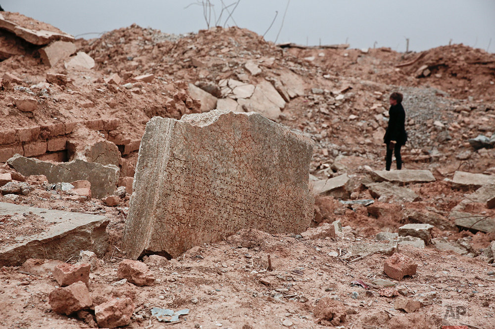 A stone tablet with cuneiform writing is seen in the foreground as UNESCO's Iraq representative Louise Haxthausen documents the damage wreaked by the Islamic State group at the ancient site of Nimrud, Iraq in this Wednesday, Dec. 14, 2016 photo. One of the Mideast's most important archaeological sites, the nearly 3,000-year-old remains of an Assyrian capital had been a trove of ancient Mesopotamian art and, with hundreds of clay tablets, provided archaeologists a wealth of information on the era. (AP Photo/Maya Alleruzzo)