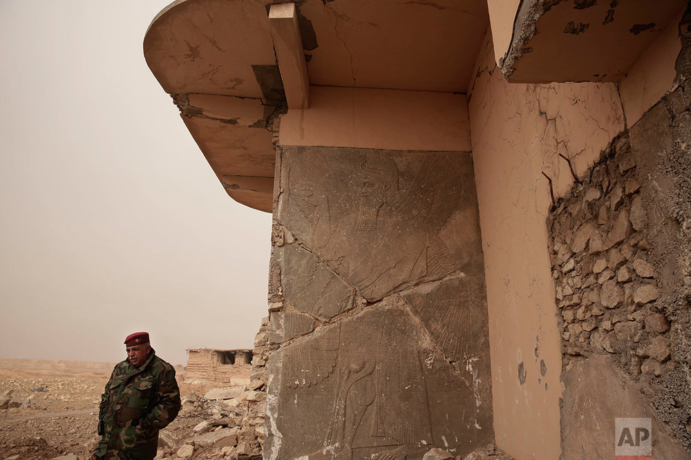 An Iraqi Army general stands near a stone slab depicting a winged genie at the entrance to the Northwest Palace at the ancient site of Nimrud, Iraq in this Wednesday, Dec. 14, 2016 photo. The Islamic State group militants who destroyed the remains of the nearly 3,000-year-old city have been driven away. But with the war still raging nearby, no one has been assigned to guard the site and the wreckage strewn around it is vulnerable to looting. (AP Photo/Maya Alleruzzo)