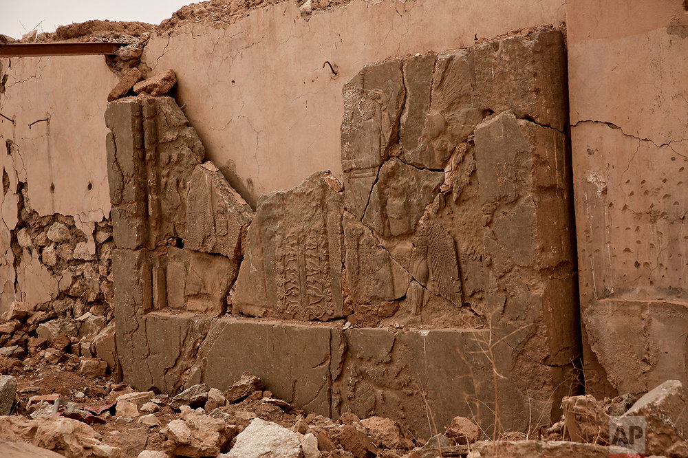 An ancient relief lies shattered in the Northwest Palace at the nearly 3,000-year-old site of Nimrud, Iraq, in this Wednesday, Dec. 14, 2016 photo. The destruction wreaked by Islamic State group militants at the site was extensive, leaving chunks of ancient reliefs, pieces of statues and pieces of cuneiform writing strewn amid rubble and dirt. With no protection more than a month after IS was driven out, those pieces are vulnerable to looting.(AP Photo/Maya Alleruzzo)