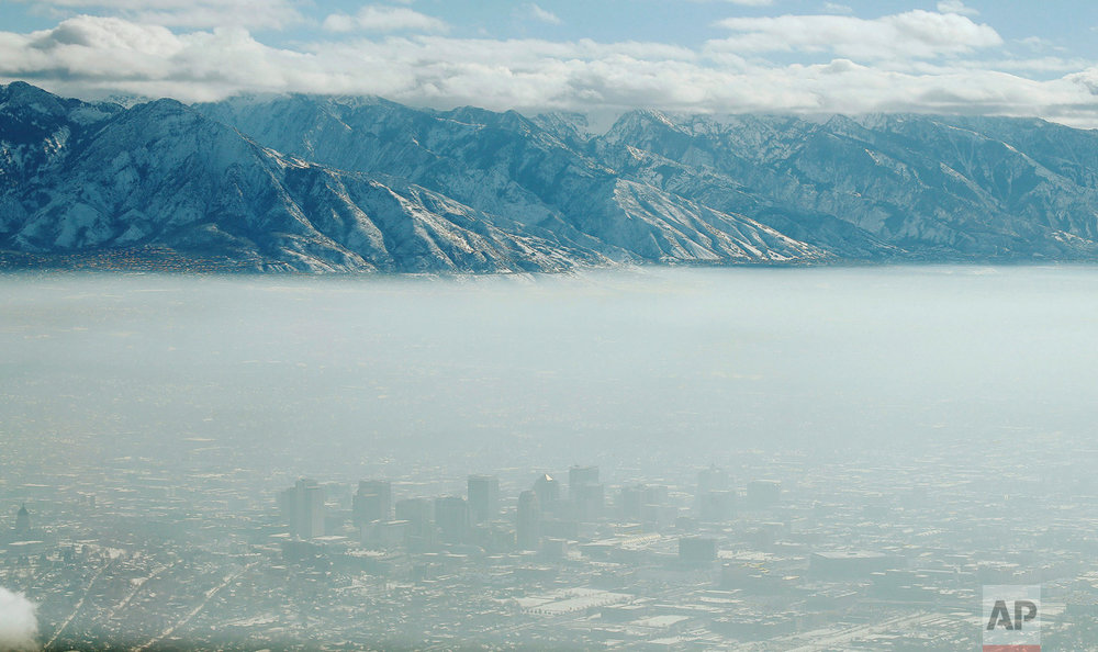 The downtown skyline of Salt Lake City, Utah is shrouded in haze during an inversion on Wednesday, Dec. 28, 2016. In the phenomenon, cold, stagnant air settles in the bowl-shaped mountain basins, trapping tailpipe and other emissions, creating a murky haze that engulfs the metro area. (Jeffrey D. Allred/The Deseret News via AP)