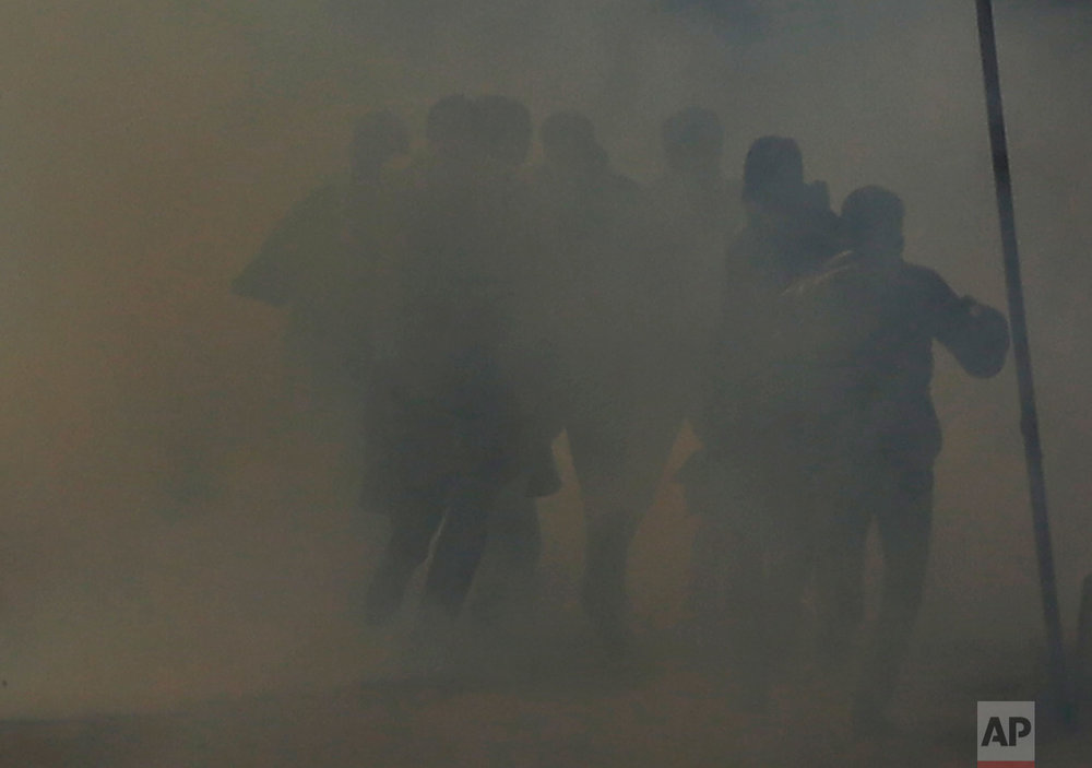 Kashmiri protesters run for cover from tear gas during a protest after Friday prayers in Srinagar, Indian-controlled Kashmir, on Friday, Dec. 30, 2016. Police fired tear gas and shotgun pellets to disperse demonstrators who gathered to protest Indian rule in the disputed region. (AP Photo/Mukhtar Khan)