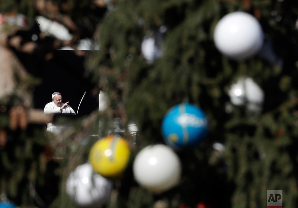 Framed by a Christmas tree, Pope Francis waves to worshippers during the Angelus noon prayer which he delivered from his studio window overlooking St. Peter's Square at the Vatican, on Monday, Dec. 26, 2016. Speaking to thousands gathered to celebrate the feast day of St. Stephen, the first Christian martyr, Francis expressed his ''strong condolences'' to the Russian people and to those who lost loved ones in a military plane which crashed shortly after take off from the city of Sochi on Sunday. (AP Photo/Gregorio Borgia)