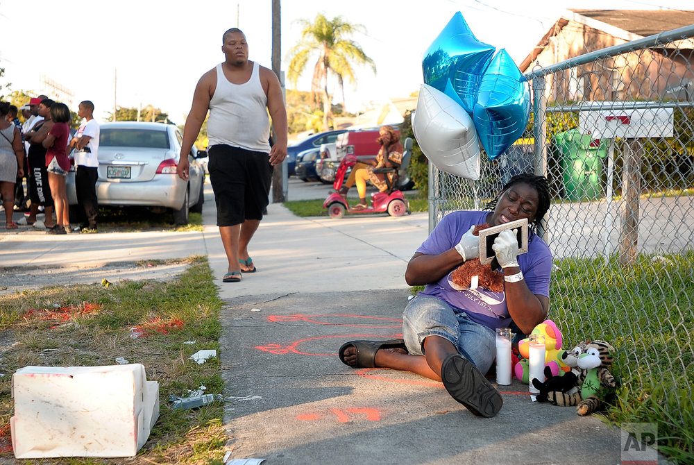 Caprice Cunningham cries on Thursday, Dec. 29, 2016 at the place where her grandson, Rasheed Cunningham, Jr., 8, was fatally shot in Dania Beach, Fla. On Friday, Broward Sheriff's Office announced an arrest in connection with the gun violence in Dania Beach that killed the 8-year-old boy on Wednesday, and Christopher Jordan, 25, on Christmas Day. (Michael Laughlin/South Florida Sun-Sentinel via AP)