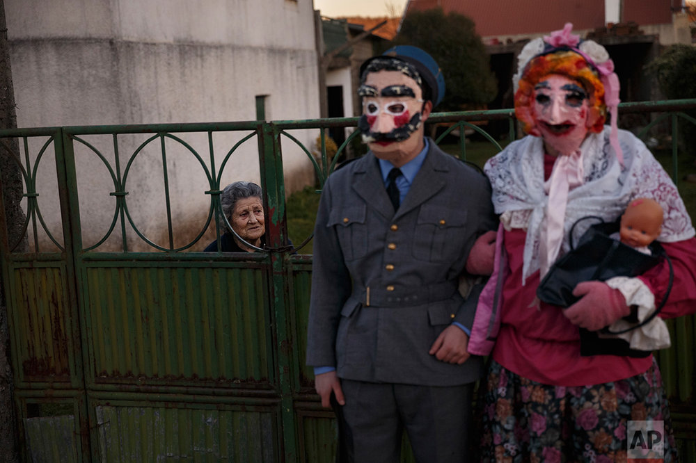 In this photo taken on Saturday, Jan. 7, 2017, a couple dressed as characters from 'la Vaquilla' wearing ancient masks pose for a photo, during a winter masquerade gathering in Salsas, Portugal. (AP Photo/Daniel Ochoa de Olza)