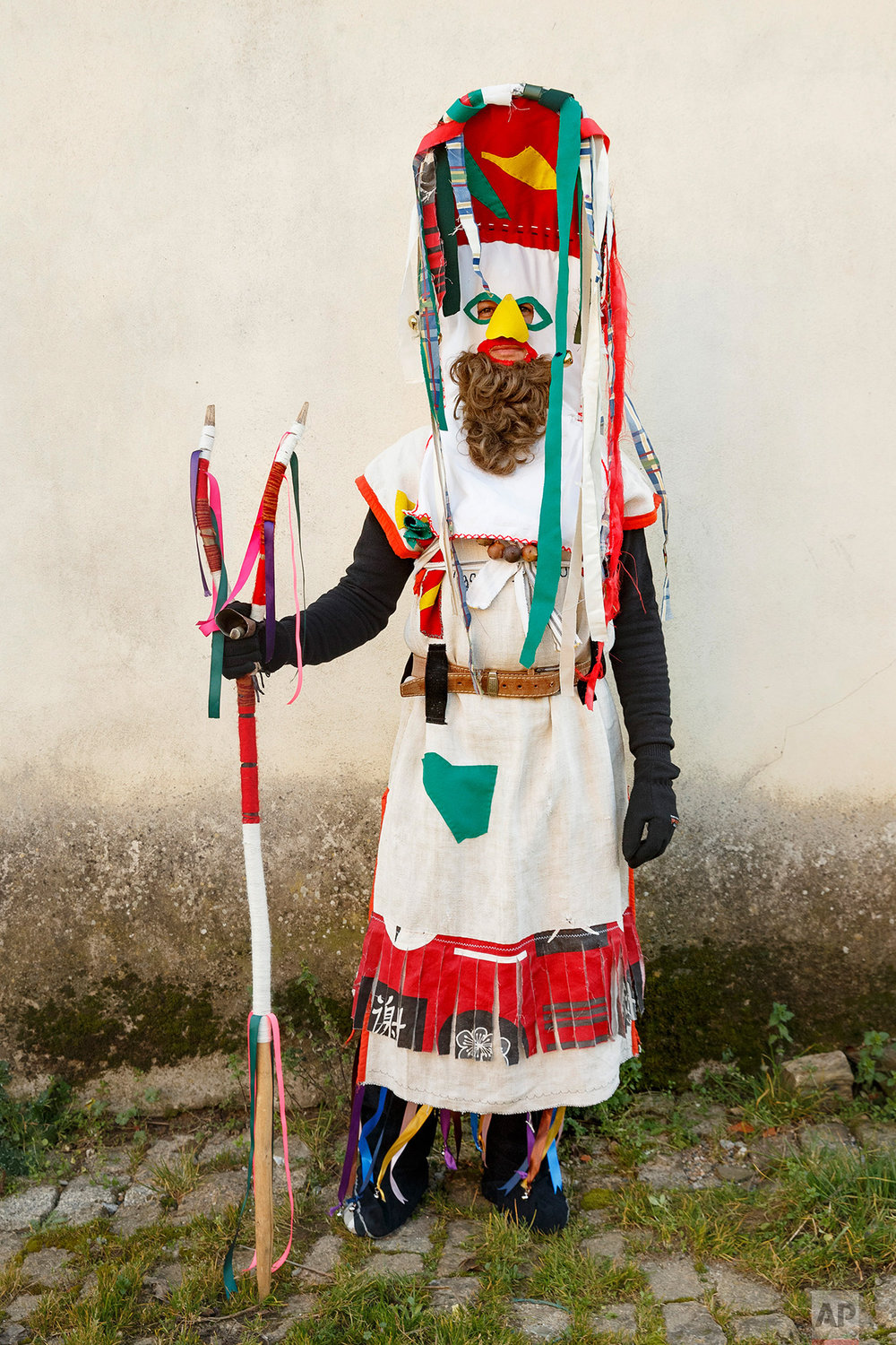 In this photo taken on Saturday, Jan. 7, 2017, a person dressed as a character from 'Visparro de Vigo' masquerade wearing an ancient mask poses for a photo, during a winter masquerade gathering in Salsas, Portugal.  (AP Photo/Daniel Ochoa de Olza)