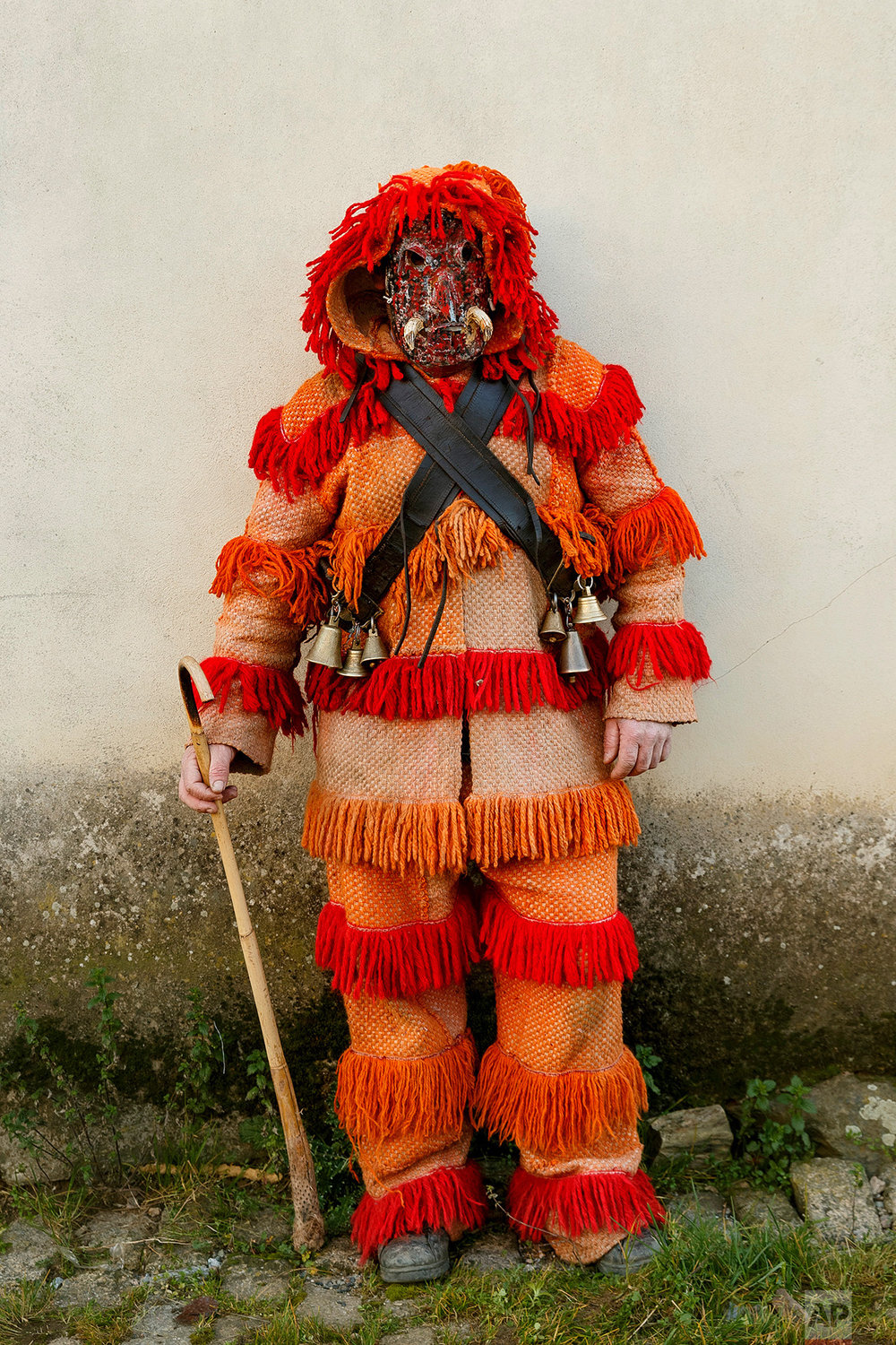 In this photo taken on Saturday, Jan. 7, 2017, a person dressed as a character from the 'Careto de Salsas' masquerade, wearing an ancient mask poses for a photo, during a winter masquerade gathering in Salsas, Portugal. (AP Photo/Daniel Ochoa de Olza)