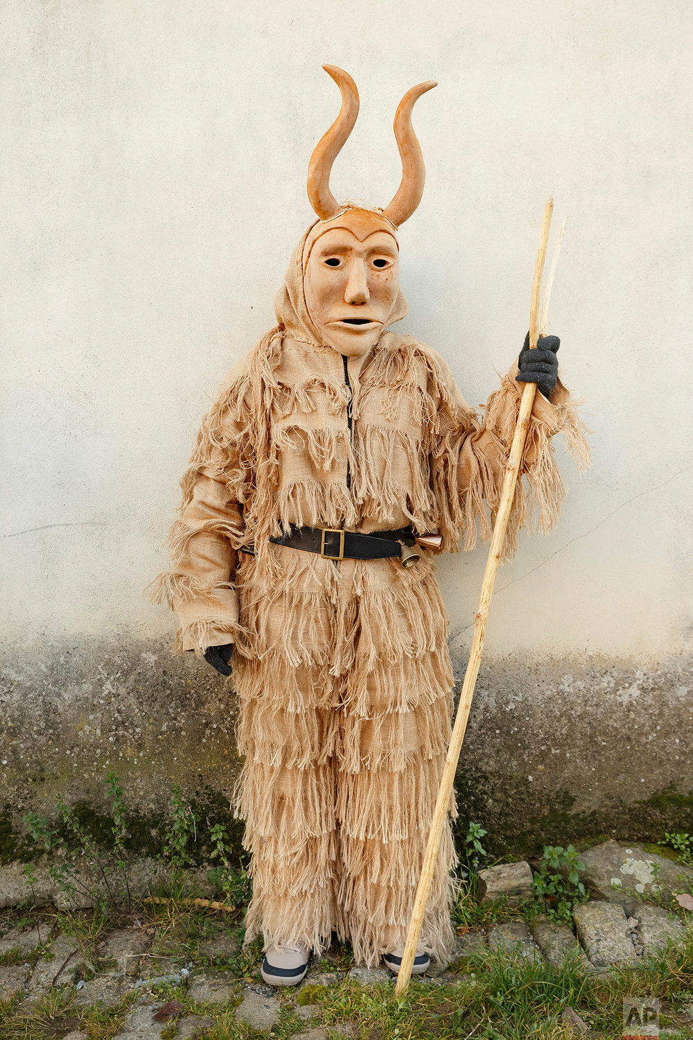 In this photo taken on Saturday, Jan. 7, 2017, a 'Careto de Lazarim' wearing an ancient mask poses for a photo, during a winter masquerade gathering in Salsas, Portugal. (AP Photo/Daniel Ochoa de Olza)