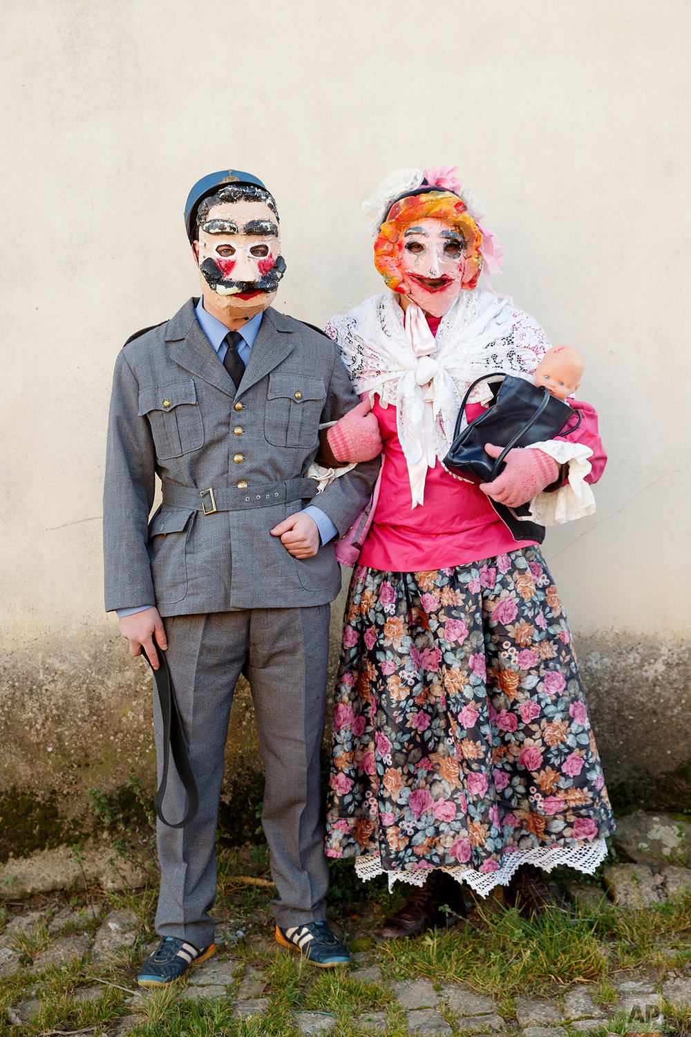 In this photo taken on Saturday, Jan. 7, 2017, a couple dress as characters from 'la Vaquilla' wear ancient masks as they pose for a photo, during a winter masquerade gathering in Salsas, Portugal. (AP Photo/Daniel Ochoa de Olza)