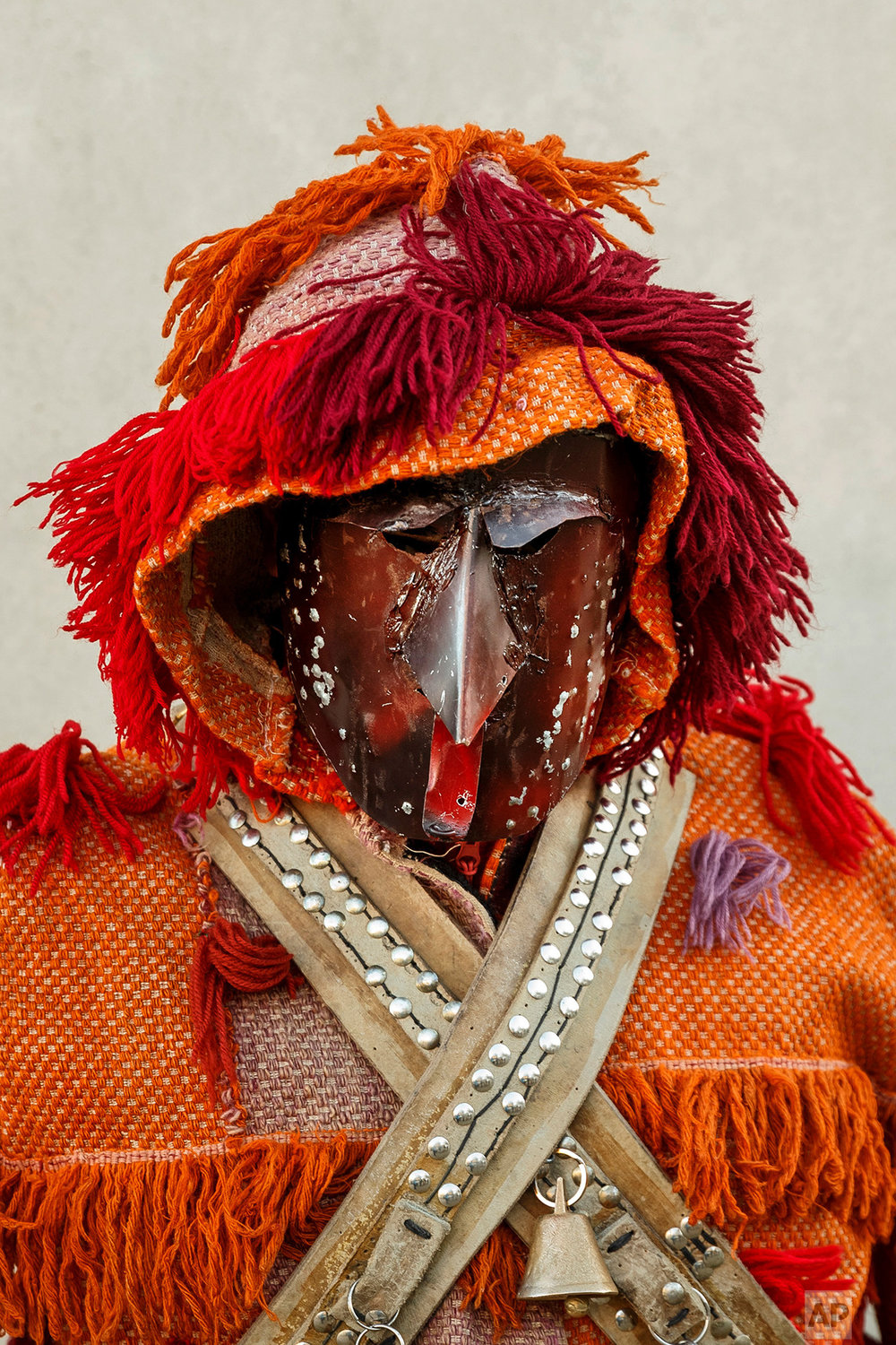 In this photo taken on Saturday, Jan. 7, 2017, a person dressed as a character from the 'Careto de Salsas' masquerade wearing an ancient mask poses for a photo, during a winter masquerade gathering in Salsas, Portugal. (AP Photo/Daniel Ochoa de Olza)