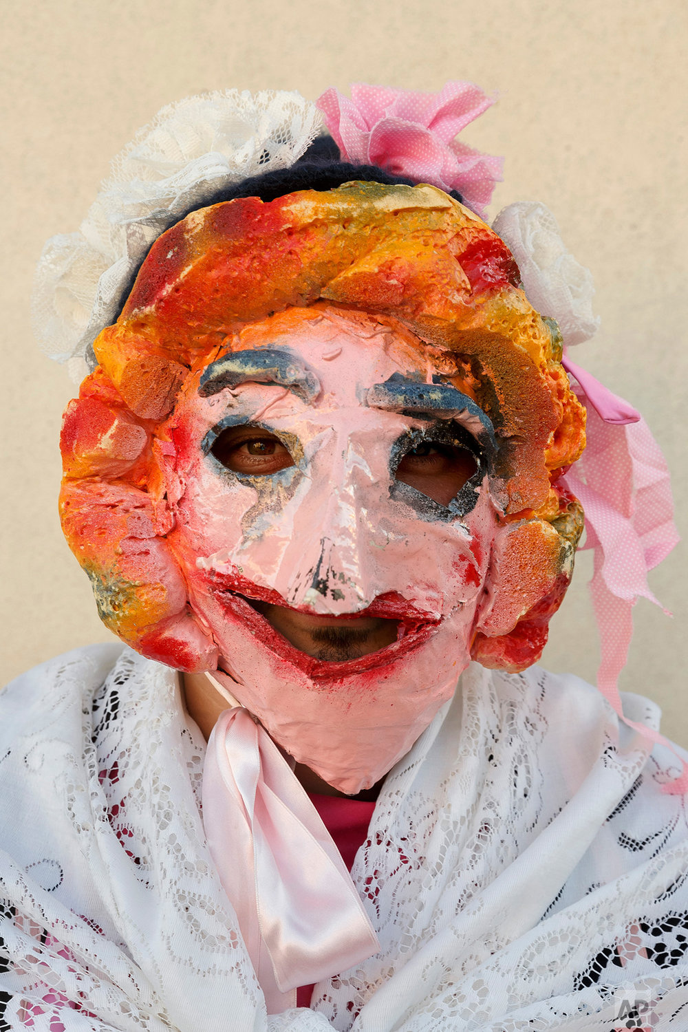 In this photo taken on Saturday, Jan. 7, 2017, a person dresses as a character from 'la Vaquilla' wearing an ancient mask poses for a photo, during a winter masquerade gathering in Salsas, Portugal.  (AP Photo/Daniel Ochoa de Olza)