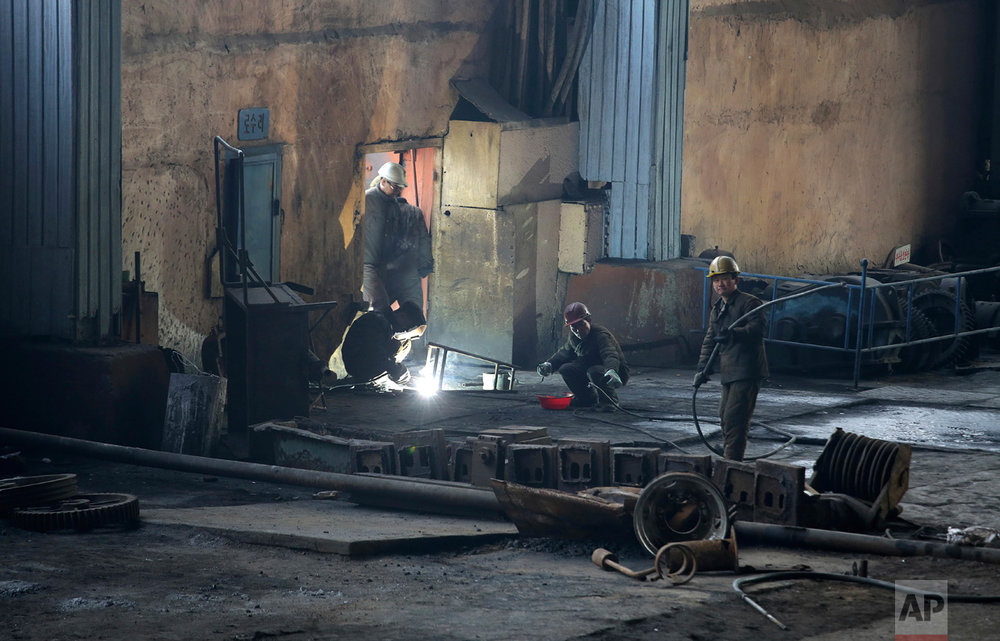 In this Saturday, Jan. 7, 2017 photo, North Korean men work at the Chollima Steel Complex in Nampo, North Korea. North Korean officials and factory managers are scrambling to answer a call from leader Kim Jong Un for an all-out, nationwide effort to build up the country's economy in 2017. The sprawling Chollima complex south of Pyongyang, the capital, is a focal point of North Korea's effort to expand the economy and lift the nation's standard of living. One of seven North Korean steel works, Chollima has more than 8,000 workers and is among the North's showcase enterprises. (AP Photo/Wong Maye-E)