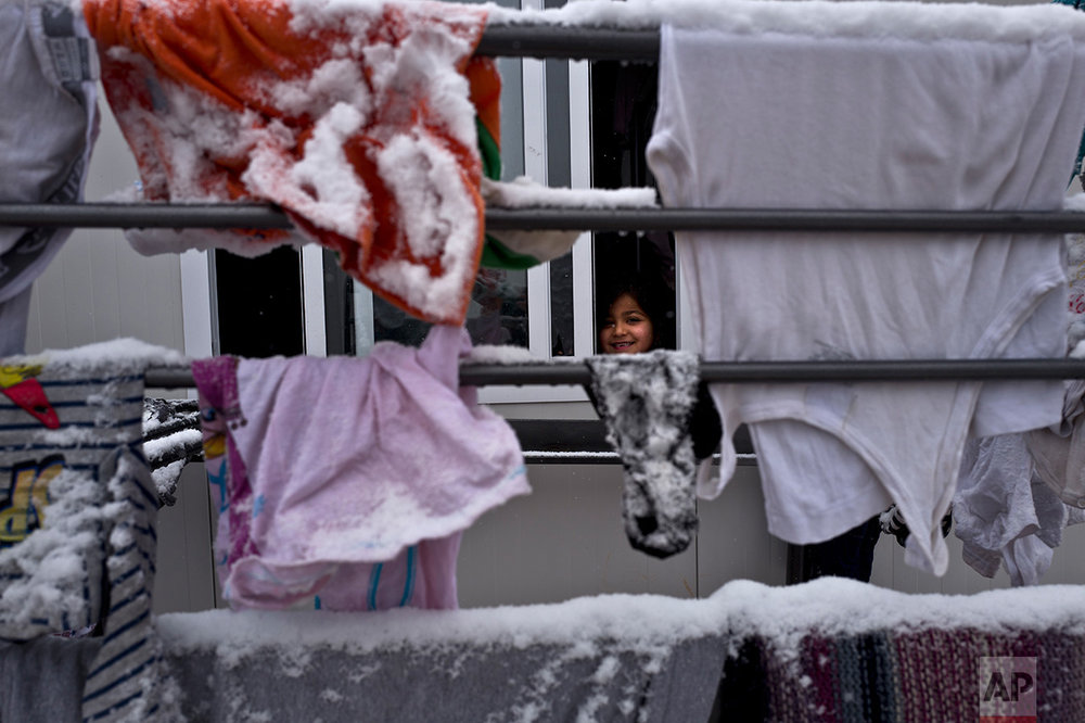A Syrian refugee girl looks out her family's shelter during snowfall at the refugee camp of Ritsona about 86 kilometers (53 miles) north of Athens, Saturday, Jan. 7, 2017. (AP Photo/Muhammed Muheisen)