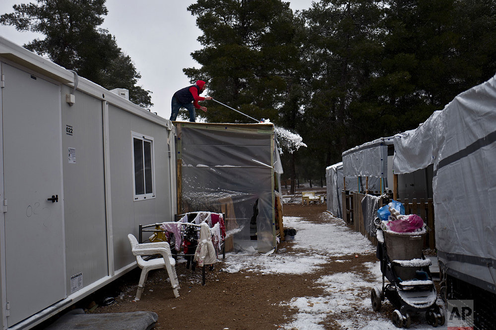A Syrian refugee man clears the rooftop of his shelter from the snow at the refugee camp of Ritsona about 86 kilometers (53 miles) north of Athens, Saturday, Jan. 7, 2017. (AP Photo/Muhammed Muheisen)