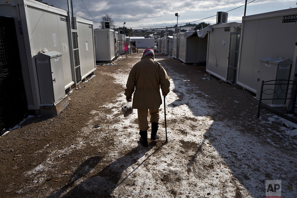 An elderly Syrian refugee man walks back to his shelter on a frozen ground at the refugee camp of Ritsona about 86 kilometers (53 miles) north of Athens, Monday, Jan. 9, 2017.  Over 62,000 refugees and migrants are stranded in Greece after a series of Balkan border closures and an European Union deal with Turkey to stop migrant flows. (AP Photo/Muhammed Muheisen)