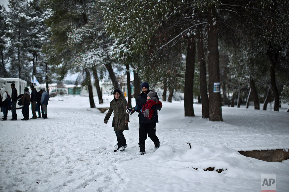 A Syrian refugee family walks back to their shelter at the refugee camp of Ritsona about 86 kilometers (53 miles) north of Athens, Tuesday, Jan. 10, 2017. (AP Photo/Muhammed Muheisen)