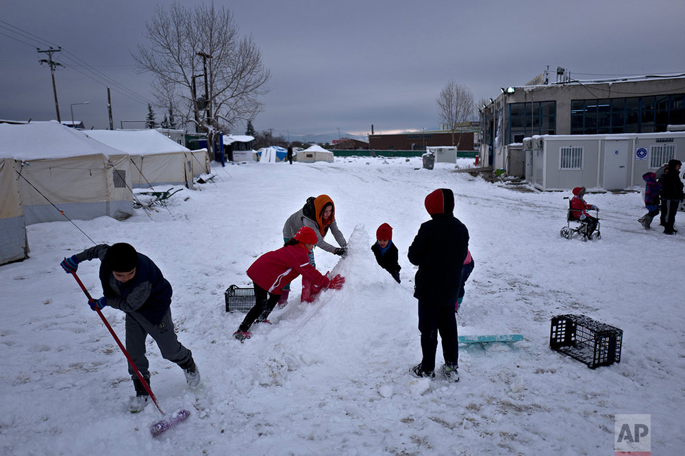 Afghan refugee children build a snowman at the refugee camp of Oinofyta about 58 kilometers (36 miles) north of Athens, Tuesday, Jan. 10, 2017. (AP Photo/Muhammed Muheisen)