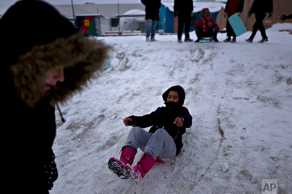 An Afghan refugee boy slides while he and other children play at the refugee camp of Oinofyta about 58 kilometers (36 miles) north of Athens, Tuesday, Jan. 10, 2017. (AP Photo/Muhammed Muheisen)
