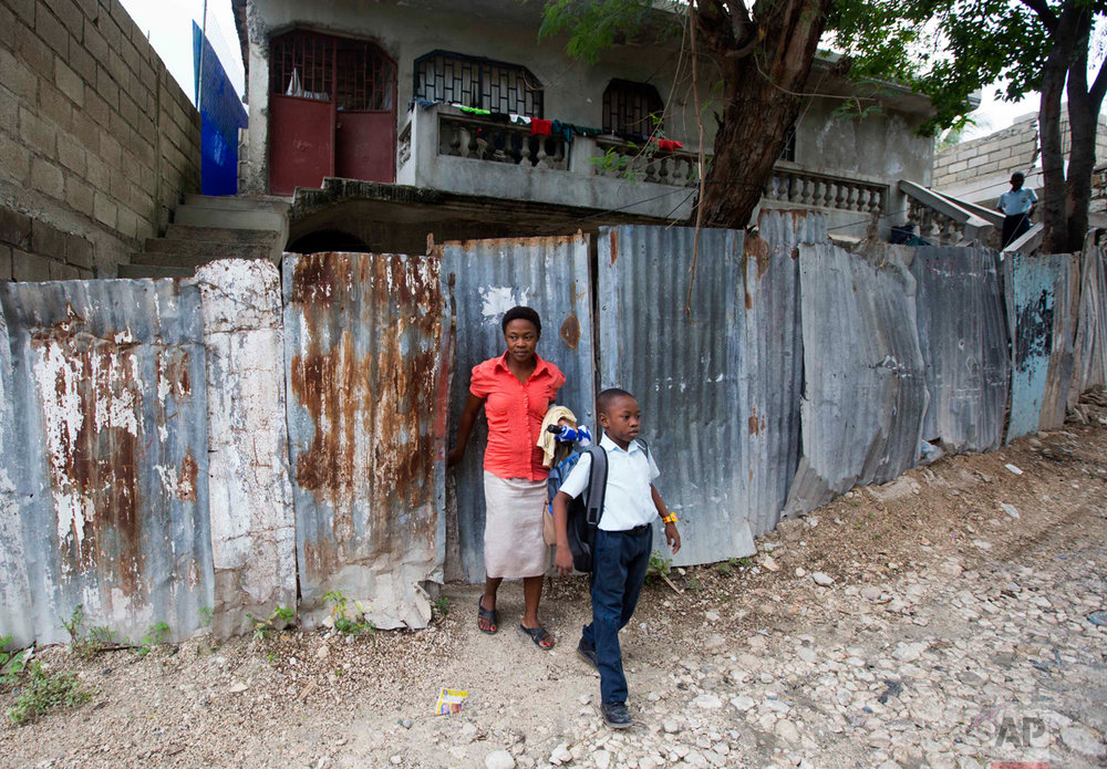 In this Jan. 10, 2017 photo, Nerlande Jean Philippe escorts her son Judeley Hans Debel, who walks on a prosthetic right leg, to his transportation to school in Petion-Ville, Haiti. Judeley's unemployed mother says free weekly sessions of therapeutic horse riding offer her son a welcome respite from a life of urban poverty. (AP Photo/Dieu Nalio Chery)