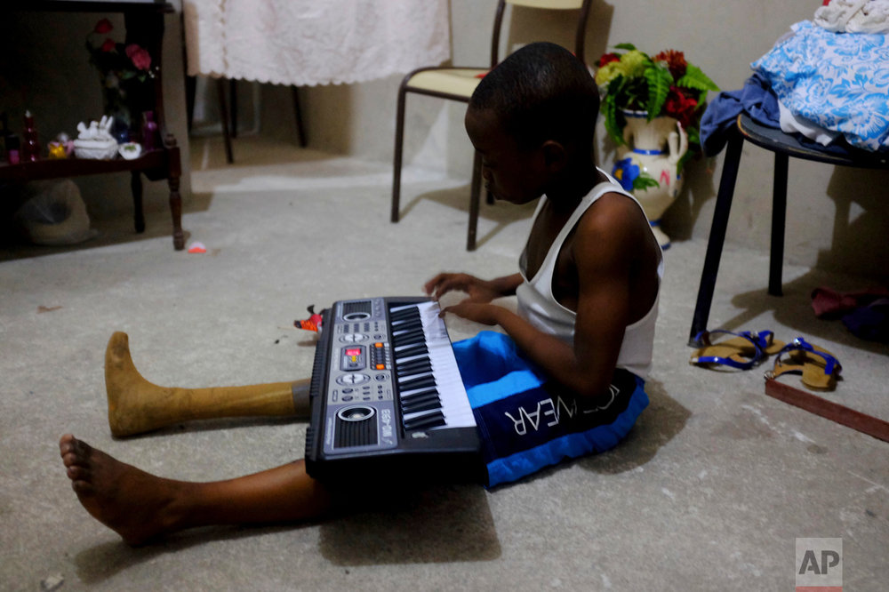 In this Jan. 8, 2017 photo, Judeley Hans Debel, whose right leg is a prosthesis, plays an electric piano at his home in Petion-Ville, Haiti. Judeley was one of an estimated 4,000 to 6,000 people to undergo amputations after the powerful earthquake that devastated Haiti's capital seven years ago. (AP Photo/Dieu Nalio Chery)