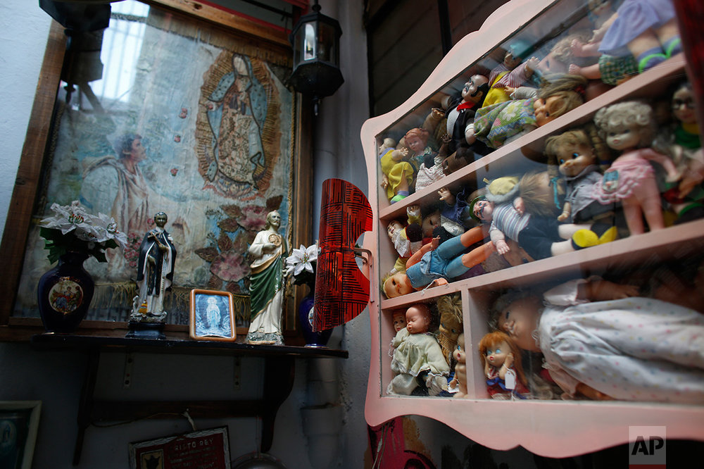 In this Jan. 11, 2017 photo, dolls stuff a display next to an altar to the Virgin of Guadalupe in the Mexico Antique Toy Museum in Mexico City. The museum is having to struggle following a congressional decision to stop allocating cultural funds for the collection. The museum has had to cut staff by half and most of its cultural events and workshops have been suspended, says the son, who hopes to raise money for the museum through a Kickstarter campaign.(AP Photo/Dario Lopez-Mills)