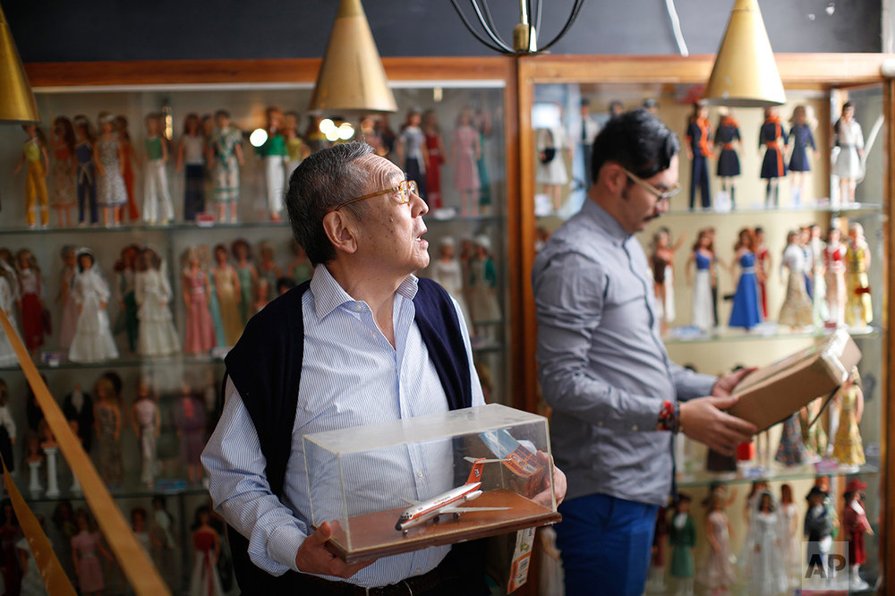 In this Jan. 6, 2017 photo, the founder of the Mexico Antique Toy Museum, Roberto Shimizu, left, and his son, Roberto, arrange objects prior to the opening of a temporary Barbie Doll exhibit in Mexico City. Even as a child, Roberto Shimizu loved collecting things. So when his Japanese immigrant father opened a stationary and toy store in the Mexican capital in 1940, Shimizu began a lifelong quest to save and collect toys. More than seven decades years later that youthful fascination lives on the Antique Toy Museum, a four-story building packed with objects that take transport visitors back to a nostalgic past. (AP Photo/Dario Lopez-Mills)