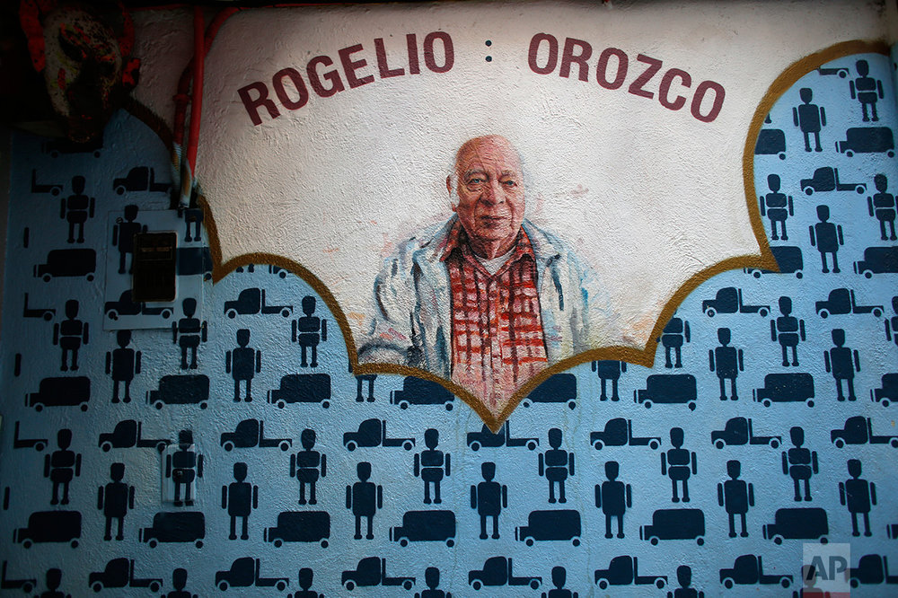 In this Jan. 11, 2017 photo, a mural painted by South African artist Christiaan Conradie depicting Mexican toymaker Rogelio Orozco graces a wall of the Mexico Antique Toy Museum in Mexico City. Orozco continues to make toy trucks and trains made out of tin with electric motors. The museum reminds Mexicans of their rich cultural heritage as well as a blunt reminder that before the North American Free trade agreement was signed in the 1990's, Mexico had a robust, healthy and creative national toy industry that is now practically defunct.(AP Photo/Dario Lopez-Mills)