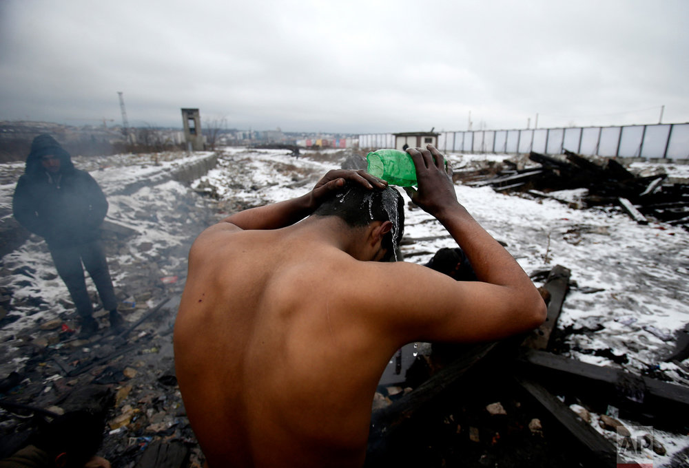 In this Saturday, Jan. 14, 2017 photo, a migrant washes himself outside a crumbling warehouse that has served as a makeshift shelter in Belgrade, Serbia. When the weather suddenly turned nasty, it sent temperatures plummeting way below zero and cold wind started to blow pushing into every corner of the make-shift migrant shelter. (AP Photo/Darko Vojinovic)