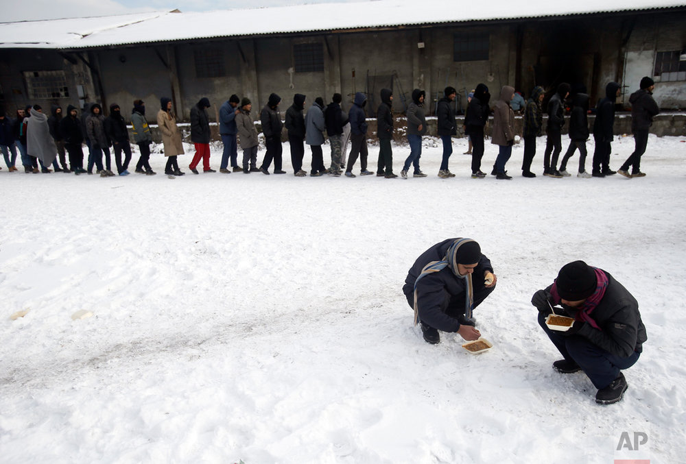 In this Thursday, Jan. 12, 2017 photo, migrants squat in the snow as they eat warm meals distributed by aid groups as others queue for their portion outside a crumbling warehouse that has served as a makeshift shelter in Belgrade, Serbia. (AP Photo/Darko Vojinovic)