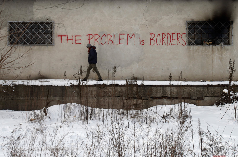 In this Thursday, Jan. 12, 2017 photo, a migrant walks through a crumbling warehouse that has served as a make-shift shelter for hundreds of men wishing to reach Western Europe, in Belgrade, Serbia. (AP Photo/Darko Vojinovic)