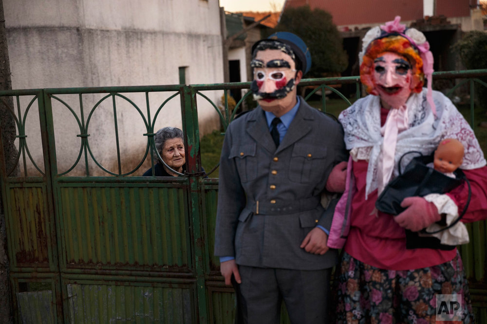 "A couple dressed as characters from the movie ""La Vaquilla"" wear masks as they pose for a photo, during a winter masquerade gathering in Salsas, Portugal on Saturday, Jan. 7, 2017. Many of these masquerades are of ancient origin and can often be traced to pre-Christian Celtic and often pre-Roman traditions around the renewal of fertility and life and an end of winter. (AP Photo/Daniel Ochoa de Olza)"