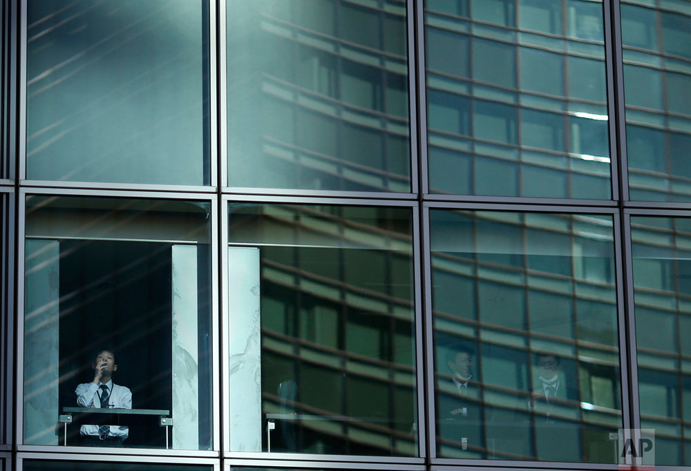 An employee looks out of a window as he smokes in a high-rise building in Tokyo on Wednesday, Jan. 11, 2017. (AP Photo/Shuji Kajiyama)