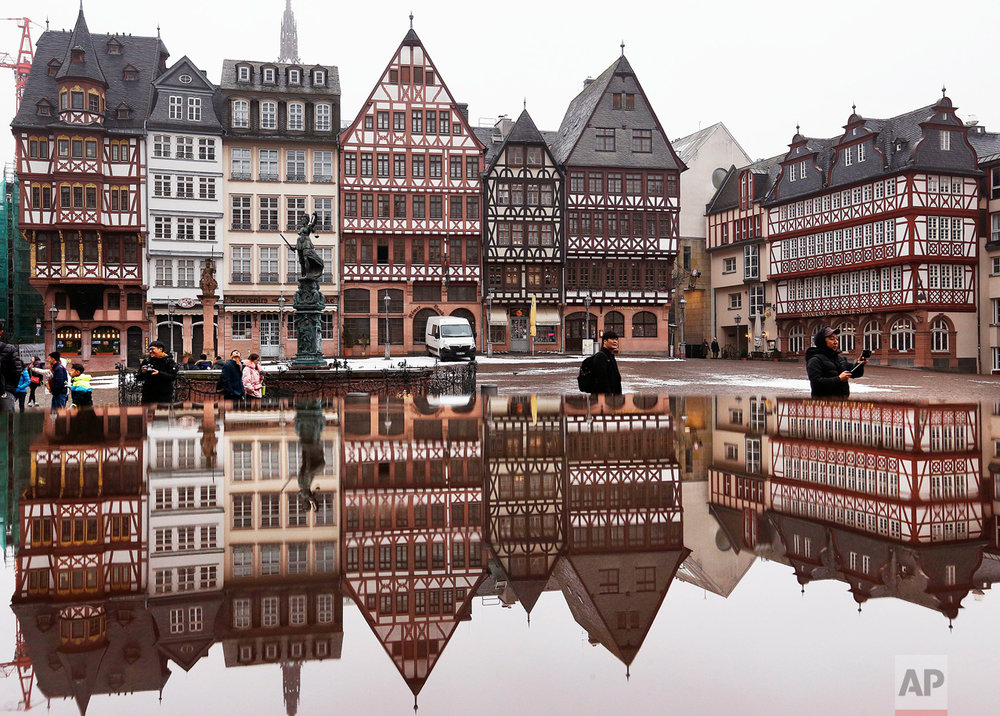 Timber frame houses at Frankfurt, Germany's Roemerberg square are reflected in water on Wednesday, Jan. 11, 2017. (AP Photo/Michael Probst)