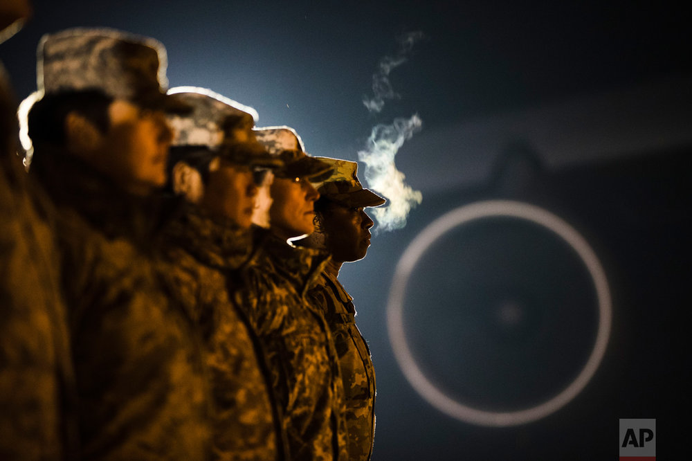 Members of the military wait for an Army carry team to move a transfer case containing the remains of Spc. Isiah L. Booker at Dover Air Force Base, Del., Wednesday, Jan. 11, 2017. According to a statement from the Department of Defense, Booker of Cibolo, Texas, died Jan. 7, in a non-combat related incident while in Jordan supporting Operation Inherent Resolve. (AP Photo/Matt Rourke)