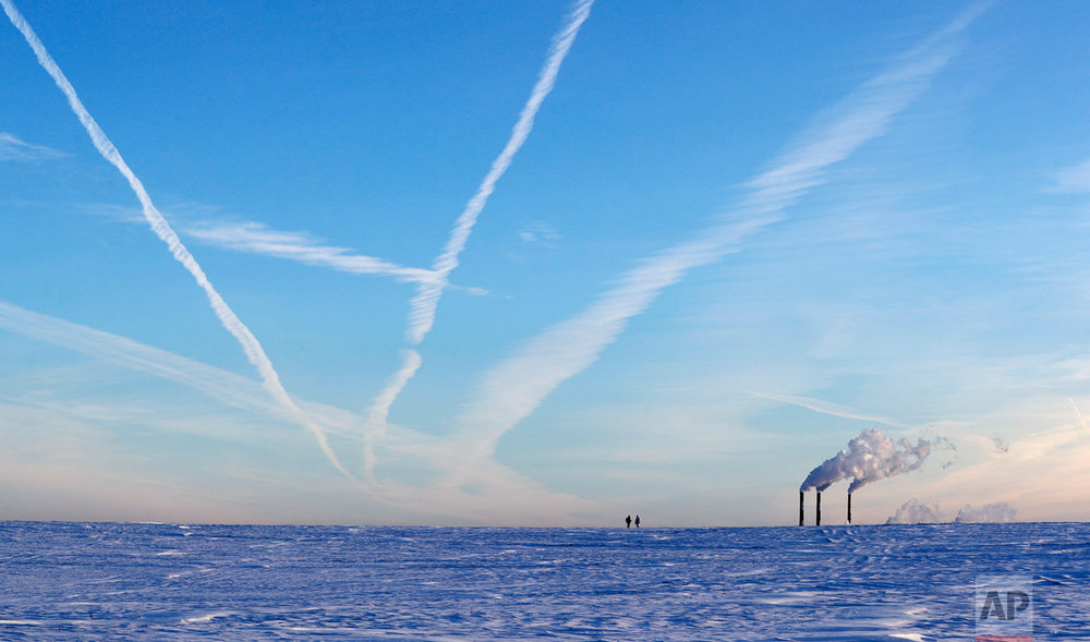 People hunting small animals search the terrain as plumes rise from a heating plant with morning temperatures of -19 degrees Celsius (-2.2 degrees Fahrenheit) in Minsk, Belarus, Monday, Jan. 9, 2017. (AP Photo/Sergei Grits)