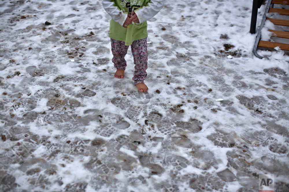 "A Syrian refugee child walks barefoot on frozen ground at the Ritsona, Greece refugee camp, about 86 kilometers (53 miles) north of Athens, on Wednesday, Jan. 11, 2017. The European Commission said conditions for refugees on islands and other camps where they are housed in tents in severe cold weather is ""untenable."" (AP Photo/Muhammed Muheisen)"