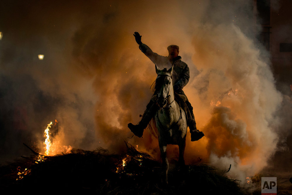 A man rides a horse through a bonfire as part of a ritual in honour of Saint Anthony the Abbot, the patron saint of domestic animals, in San Bartolome de Pinares, about 100 km west of Madrid, Spain, on Monday, Jan. 16, 2017. (AP Photo/Emilio Morenatti)