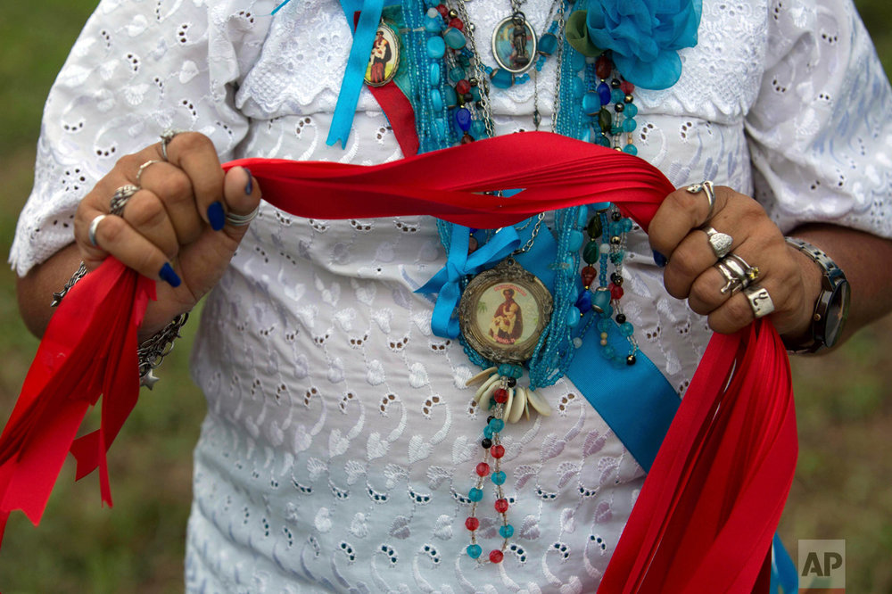 This Dec. 25, 2016 photo shows a woman holding red ribbons for the champion of the Cavalhada horse riding event during the Marujada religious celebration in honor of St. Benedict in the fishing town of Braganca, Brazil. Galloping horsemen compete to place a small stick through a small ring in the air. (AP Photo/Eraldo Peres)