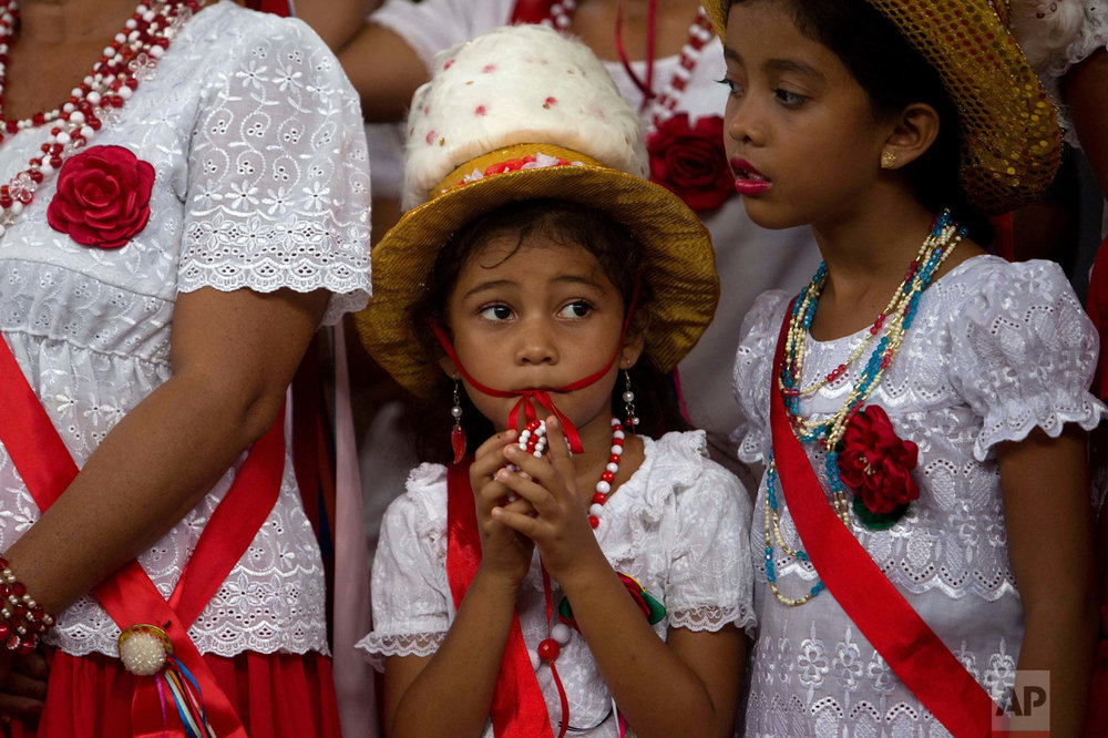 This Dec. 26, 2016 photo shows a girl attending Marujada religious celebrations in honor of St. Benedict in the fishing town of Braganca, Brazil. On this day of the days-long tradition, people dress in red, a color also seen in street decorations, as the city begins a day of partying. (AP Photo/Eraldo Peres)