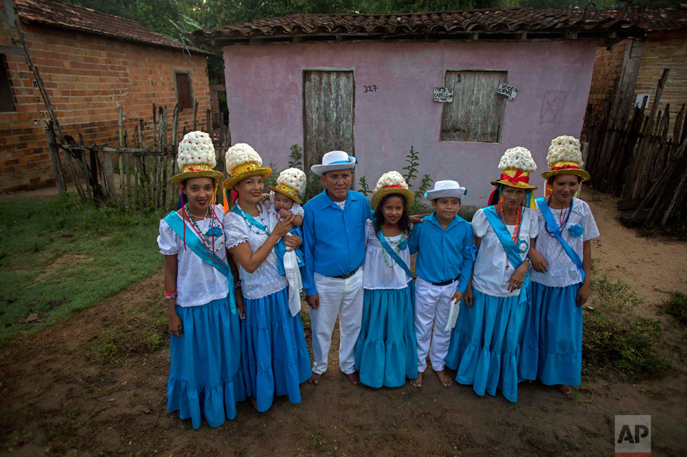 This Dec. 25, 2016 photo shows Joao Gomes, 64, center, with his family outside their home during Marujada celebrations in honor of St. Benedict in the fishing town of Braganca, Brazil. The tradition began in 1798 when black slaves persuaded their masters to let them form a brotherhood to pay homage to St. Benedict. (AP Photo/Eraldo Peres)