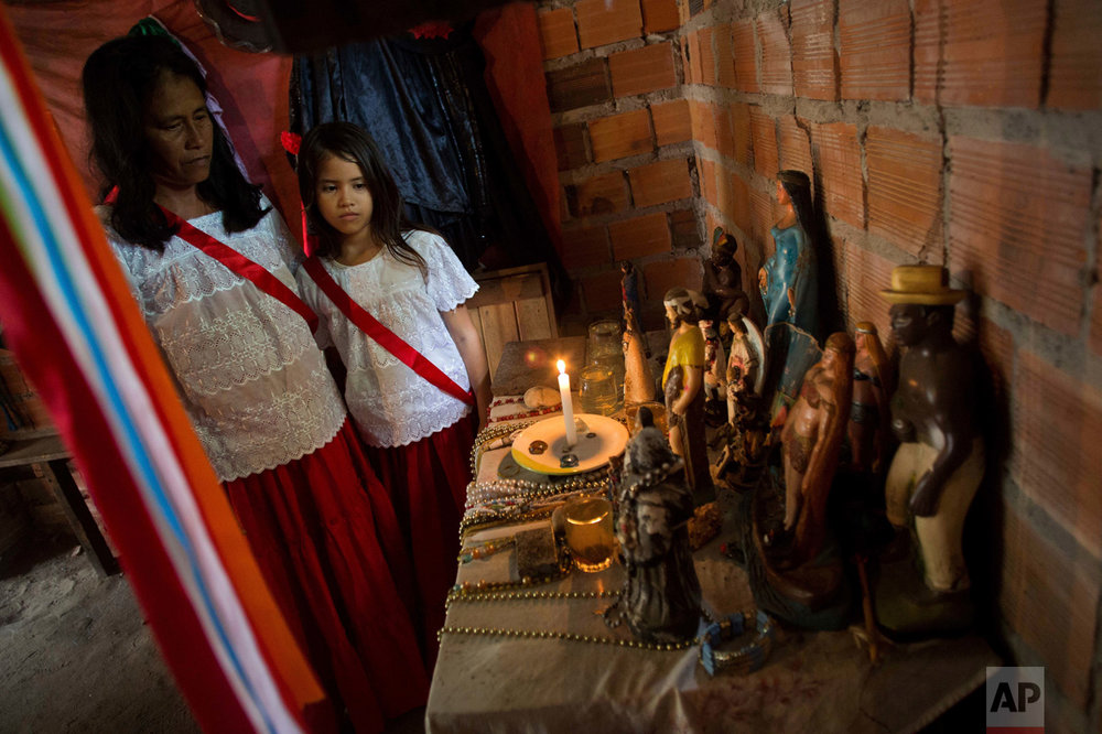 This Dec. 23, 2016 photo shows Vania Ramos and her daughter Ana Beatris standing before an altar inside their home as they prepare for Marujada religious celebrations in honor of St. Benedict in the fishing town of Braganca, Brazil. The annual celebration arose when black slaves persuaded their masters to let them pay homage to St. Benedict. (AP Photo/Eraldo Peres)