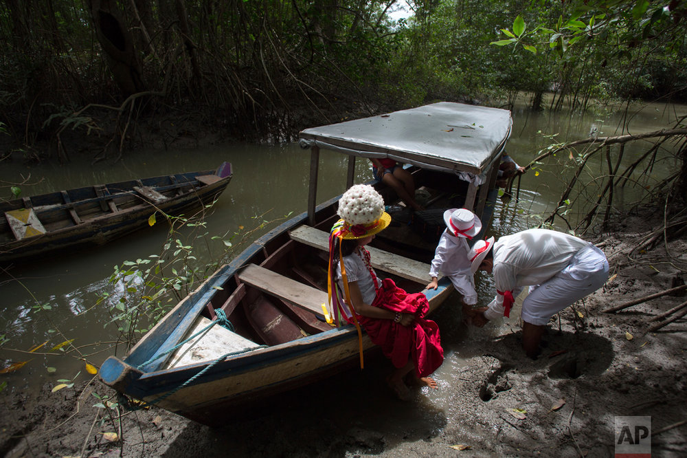 This Dec. 20, 2016 photo shows a family arriving on the Caete River to attend Marujada religious celebrations in honor of St. Benedict in the fishing town of Braganca, Brazil. Locals say the annual celebration, which started in 1798, is a way to show appreciation and make good on promises for miracles received. (AP Photo/Eraldo Peres)