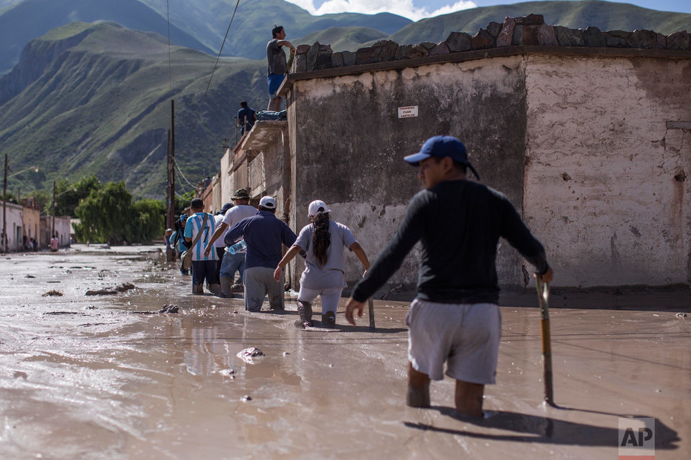 In this Jan. 13, 2017 photo, volunteers walk with shovels on the way to help clear clear the mud and help locals the town of Volcan, Jujuy province, Argentina. The mudslide was caused by the intense rains that hit the area one week ago, flooding the town with mud, killing several and causing the evacuation of thousands. (Gianni Bulacio/Infoto via AP)