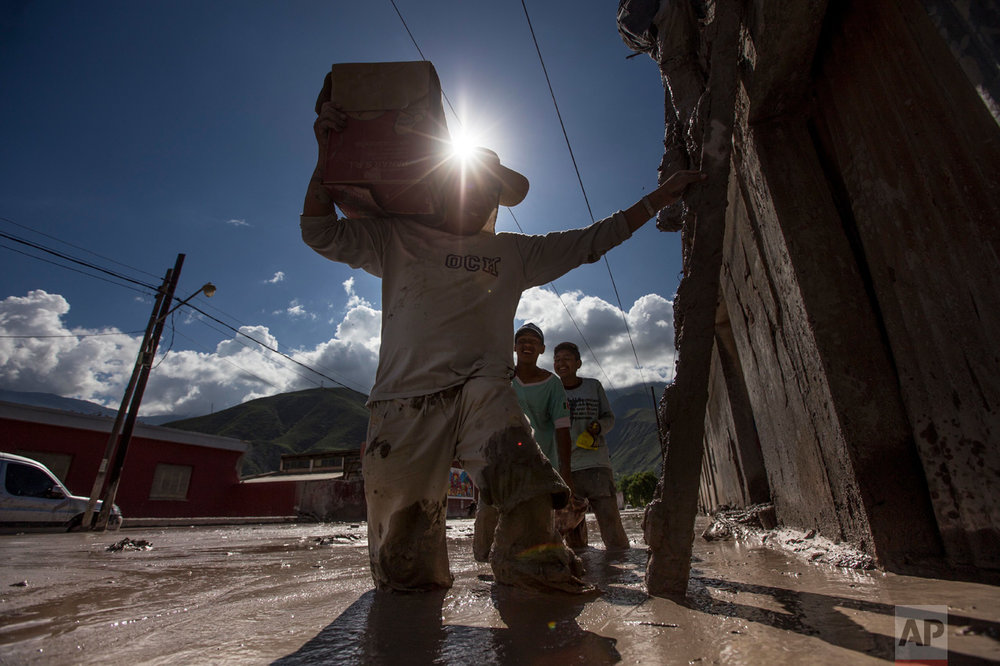 In this Jan. 13, 2017 photo, residents carry their belonging to the roofs of their mud flooded homes in the town of Volcan, Jujuy province, Argentina. Authorities declared the area a disaster zone after the town was hit by a mudslide one week ago, that covered it in a thick layer of mud. (Gianni Bulacio/Infoto via AP)