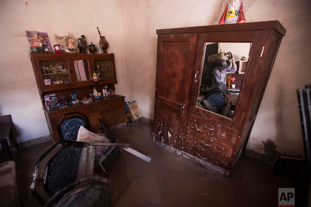 In this Jan. 13, 2017 photo, a resident carries a gas cylinder as he rescues items from his mud damaged home in the town of Volcan, Jujuy province, Argentina, Monday. The town which was hit by a mudslide one week ago, has forced the evacuation on most of its residents. Several are refusing to go, not willing to leave their belongings behind, while others help in the recovery effort. (Gianni Bulacio/Infoto via AP)