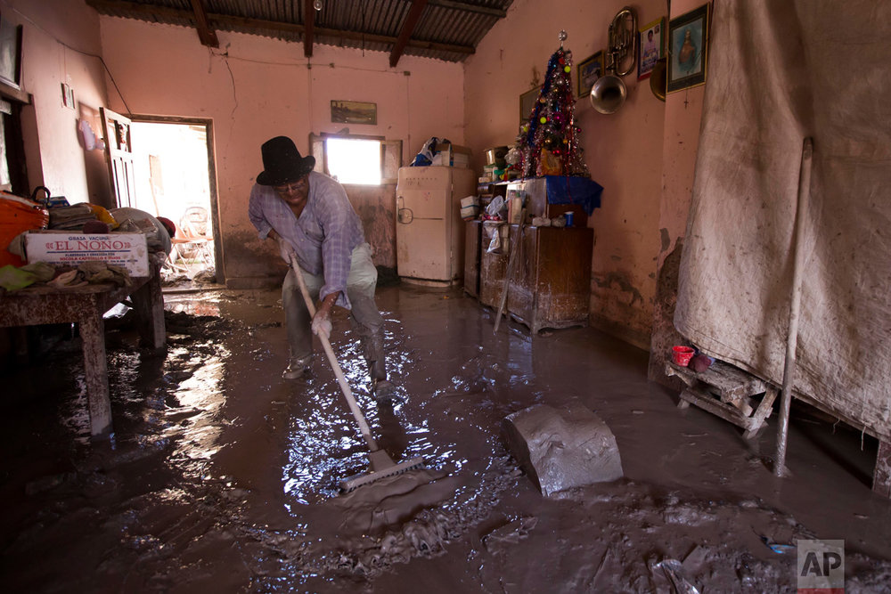 In this Jan. 13, 2017 photo, a resident begins the clean up of his mud damaged home in the town of Volcan, Jujuy province, Argentina. That town was hit by a mudslide a week ago after heavy rains blanketed the area. (Gianni Bulacio/Infoto via AP)