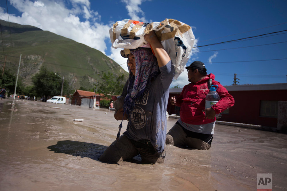 In this Jan. 13, 2017 photo, residents wade waist deep in the mud, with rescued religious figures, in the town of Volcan, Jujuy province, Argentina. The statues will be taken to a secure place until cleanup efforts are completed. (Gianni Bulacio/Infoto via AP)
